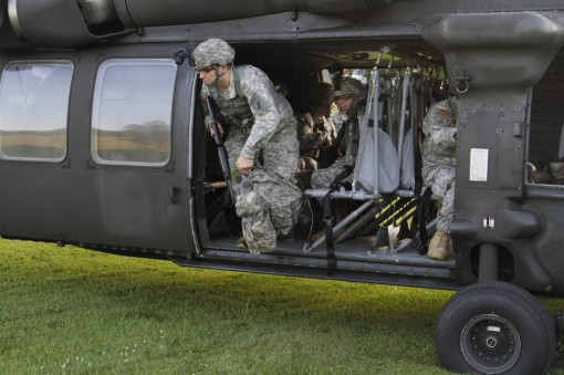 A Soldier with the Army Reserves 403rd Civil Affairs Battalion disembarks from a UH-60 Blackhawk helicopter belonging to the New York Army National Guard's  A Company, 3rd Battalion, 142nd Aviation  during a training exercise in Cooperstown, New York