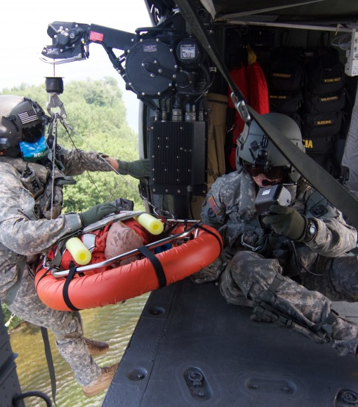 New York Army National Guard Staff Sgt. Stephen Tschiderer, a fllight medic assigned to Company F, 1st Battalion, 169th General Support Aviation Battalion,brings a simulated casualty on board a hovering UH-60 helicopter during a training exercise near Fre