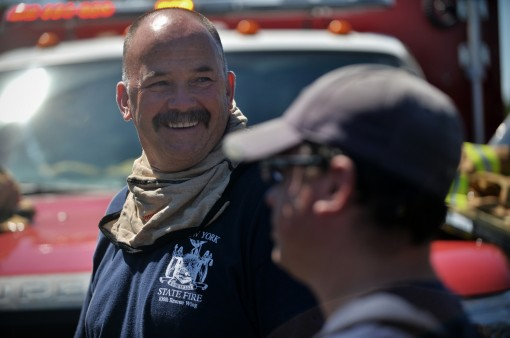 106th Rescue Wing Firefighter Michael Clay talks with Ronnie Tedesco, Christopher Clay and New York Air National Guard Senior Master Sgt. James Nizza after helping to put out a major brush fire just off-base at Westhampton Beach on August 10, 2015