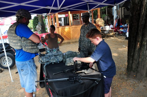 SARATOGA SPRINGS-- Visitors to the Saratoga Race Track inspect New York Army National Guard equipment at a station manned by Army Guard Recruiting and Retention Battalion during the track's Military Appreciation Day on Sept. 2, 2015.