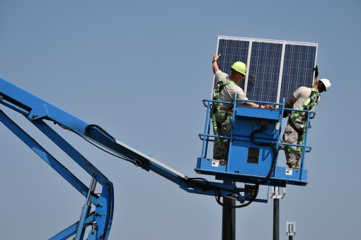 Staff Sgt. Edwin Laporte and Hector Gomez both members of the 106th Civil Engineering Squadron 106th Rescue Wing install a solar panel at FS Gabreski ANG on September 8 2015.The solar panels are part of a larger plan to reduce energy usage and save money