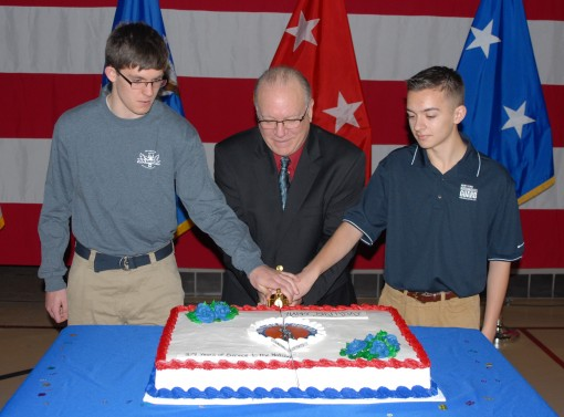 Recruits  Zander Griffin (left) and Andrew Valenza (right) join retired New York Army National Guard Chief Warrant Officer Brian Smith (center) to cut the National Guard Birthday cake