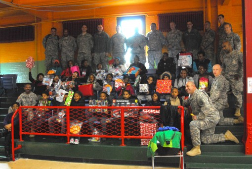 -Soldiers of the New York Army National Guard's 369th Sustainment Brigade pose with children from the Harlem Children's Zone during a toy and coat drive event at the Harlem Armory December 5 2015.  The event was organized as a way for the 369th