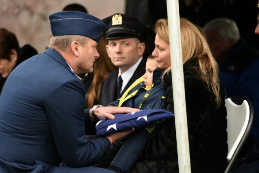 Colonel Timothy J. LaBarge, commander of the 105th Airlift Wing  presents an American flag to the wife of Tech. Sgt. Joseph G. Lemm at a funeral ceremony held on December 30, 2015. Tech. Sgt. Lemm was killed in action while deployed to Bagram Airfield, Af