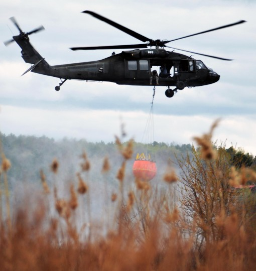A New York Army National Guard UH-60 Blackhawk based in Latham, N.Y. hovers in place while doing swift load and drop water bucket training at Round Lake N.Y.on Thursday May 5, 2016.