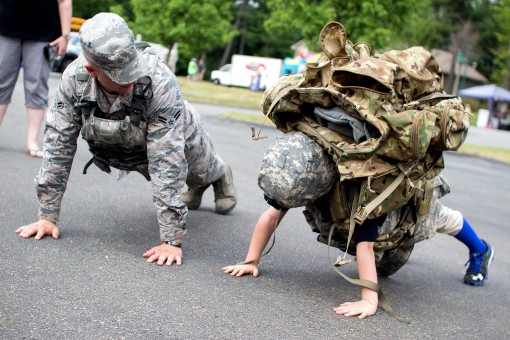 An Airman from the 105th Airlift Wings Base Defense Squadron  shares push-ups with a visitor to the Touch a Truck event held there on Saturday, June 4, 2016. The 105th Base Defense Squadron took three vehicles up to Sullivan County  to share the experienc