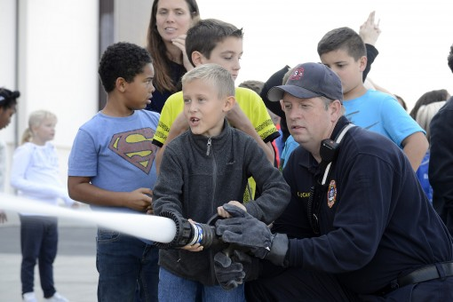 Stewart Fire Department Firefighter Daniel Lucak helps Delaware Valley School District students operate a fire hose during a tour of Stewart Air National guard Base Nov. 2, 2016. Students were able to ask questions, operate a hose and see two different ty