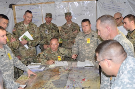 New York Army National Guard aviation Soldiers assigned to the 42nd Combat Aviation Brigade ponder their next move over a map of the area of operations in their command post during a two-week Warfighter command post exercise at Fort Indiantown Gap on Thur