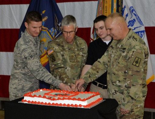 Brig. Gen. Raymond Shields assistant adjutant general Army of New York (far right) joins the oldest and newest members of the New York National Guard to cut a cake in celebration of the National Guards 380th birthday at New York National Guard headquarter