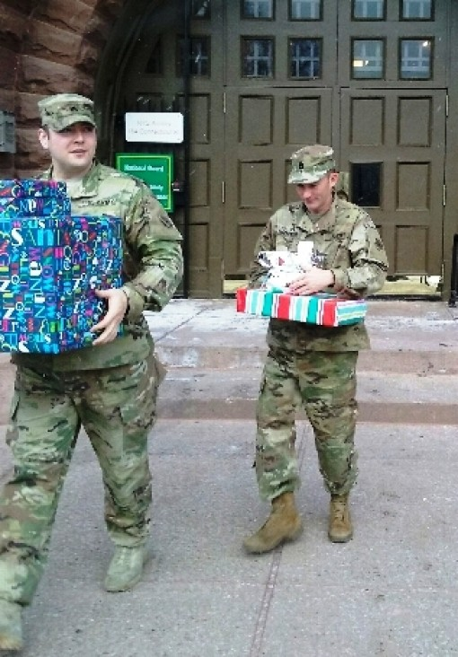 BUFFALO-- New York Army National Guard Sgt. 1st Class Ethan Unterweger ( left) and Sgt. Connor Flannery, both members of the 27th Brigade Special Troops Battalion, carry presents out of the Connecticut Street Armory, here on Dec. 21 on their way to delive