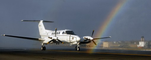 "A New York Army National Guard C12 aircraft, piloted by Chief Warrant Officer 5 Robert Wold, taxis through a rainbow at the Army Aviation Support Facility in Latham, N.Y. on Dec. 21. The rainbow formed as Wold completed his traditional military ""fina"