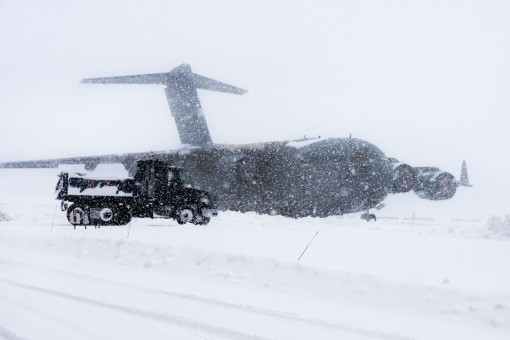 -A dump truck from the 105th Civil Engineer Squadron of the 105th Airlift Wing of the New York Air National Guard drives past a C-17 Globemaster III cargo plane while conducting snow clearing operations on the flight line at Stewart Air National Guard Bas