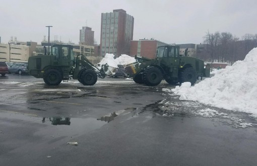 New York Army National Guard Soldiers assigned to the 827th Engineer Company clear snow from a parking lot at tehe State University of New York Binghamton on March 18 2017 as part of the New York National Guard response to the noreaster storm which covere