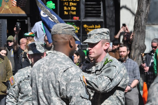 U.S. Army Captain Dennis Tierney, right, passes the colors of the New York Army National Guard's Company A, 1st Battalion, 69th Infantry to his first sergeant, Sgt. 1st Class Jairo Aquino, following his assumption of command ceremony in New York City