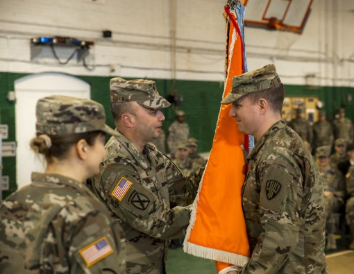 U.S. Army Maj. Ian Seagriff accepts the flag of the 101st Expeditionary Signal Battalion of the New York Army National Guard, from Brig. Gen. Michel Natali, the commander of the 53rd Troop Command as he assumes command of the battalion from outgoing comma