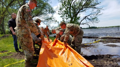 New York Army National Guard Soldiers deploy the Tiger Dam flood control system along the shores of Braddock Bay in the Town of Greece, N.Y. in response to rising waters on Lake Ontario. The system consists of flexible fabric tubes which are connected and