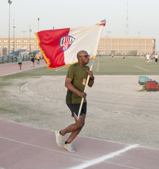 --Master Sgt. Edgar Ponce of the New York Army National Guard's 369th Sustainment Brigade carries the brigade colors over the finish line in the inaugural Harlem Hellfighter 5K run held at Camp Arifjan Kuwait on June 2 2017.