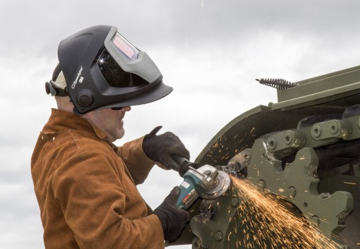 CAMP SMITH TRAINING SITE-- U.S. Army Staff Sgt. Cory Peck, a welder for the New York Maneuver Area Training Equipment Site at Ft. Drum and attached to the 1427th Transportation Company, New York Army National Guard, uses a grinder to remove paint from the