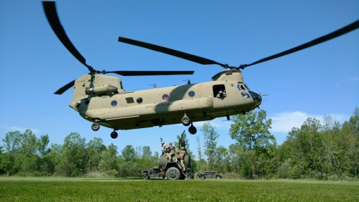 A CH-47 assigned to the New York Army National Guards Company B 3rd Battalion 126th Aviation conducts sling load training with Soldiers of Company D 427th Support Battalion who are preparing to load a water trailer at the New York National Guard training