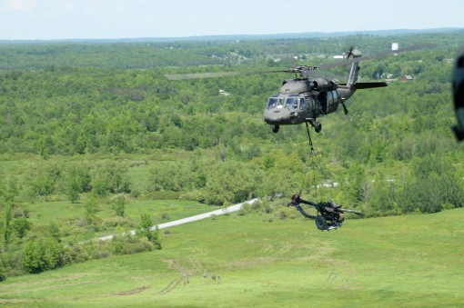 A UH-60 Black Hawk Helicopter transports a M119A2 Howitzer over Fort Drum, N.Y., June 8, 2017. Soldiers from 1st Battalion, 258th Field Artillery were conducting annual training, which involved setting up Howitzers, firing, then extracting them.