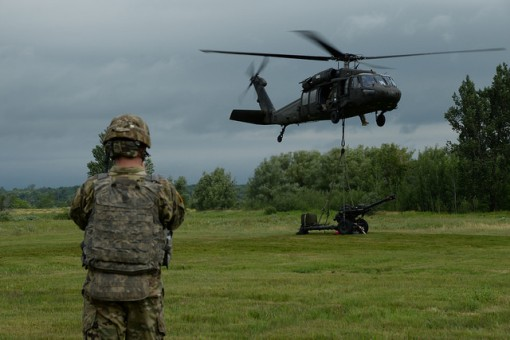 A NY Army National Guard UH-60 helicopter lifts a howitzer during training.