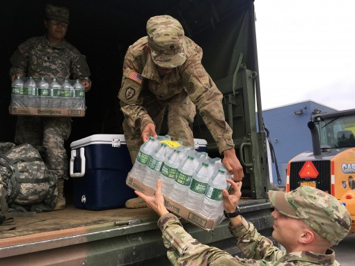 Spc. Alfred Allen center hands Sgt. Jared Kaminski a case of bottled water