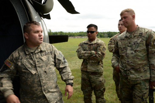 N.Y. Army National Guard Soldier, Sgt. Shawn Bradley, a crew chief with 3rd Battalion, 142nd Aviation, instructs active duty Soldiers from Bravo Battery 2nd Battalion, 15th Field Artillery Regiment, 2nd Brigade Combat Team, on how to enter a Black Hawk fo