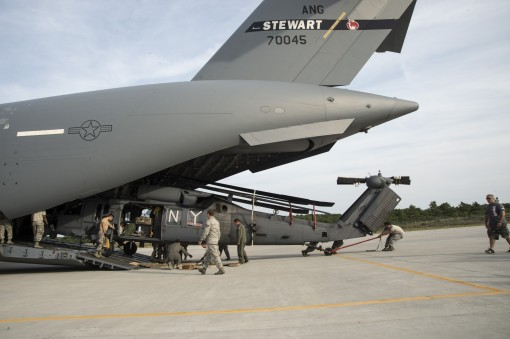 New York Air National Guard Airmen unload an HH-60 Pave Hawk helicopter from the back of a C-17 Globemaster III of the 105th Airlift Wing  at Gabreski Air National Guard Base in Westhampton Beach on Sept. 12, 2017 as deployed members of the 106th Rescuer