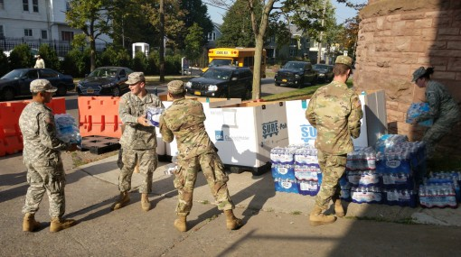 New York Army National Guard Spc. Jason Stopka, center, helps pass donated cases of water to Spc. Nigel Howard at a New York National Guard donation collection point at the Connecticut Street Armory in Buffalo, N.Y. Dulinawka, along with other Soldiers of