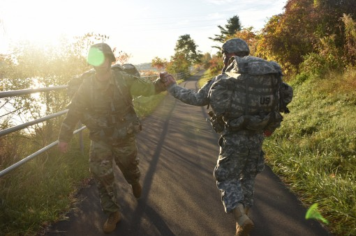 New York Army National Guard  Sgt. Kevin Baker, assigned to the 1427th Medium Truck Company, and Spc. John Iseman, assigned to the 1108th Explosive Ordnance Disposal (EOD), high-five during a 10k ruck march for the Best Warrior Competition, in Glenville,
