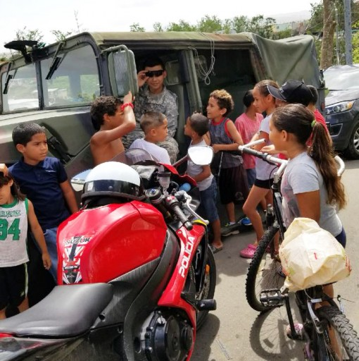 Specialist Han Wang a Soldier in the 442nd Military Police Company of the New York Army National Guard provides an impromptue Chinese lesson to kids in Toa Alta,Puerto Rico on Oct. 26. The company deployed over 120 Soldiers to Puerto Rico to assist in sec