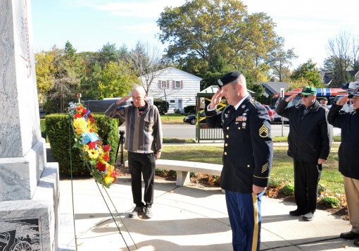New York Army National Guard Staff Sgt. Colin Stewart, from Garden City, a member of the 1st Battalion, 69th Infantry Regiment presents a memorial wreath on behalf of the Rainbow Division Veterans Foundation, at the 42nd Division Memorial in Garden City,