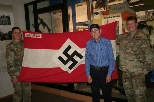 World War II Army veteran Charlie Brown of Olean New York displays his captured Hitler Youth battle flag from his combat experience in Europe as part of the 258th Field Artillery Battalion with Lt. Col. Peter Mehling right and Capt. Steven Kerr left the c
