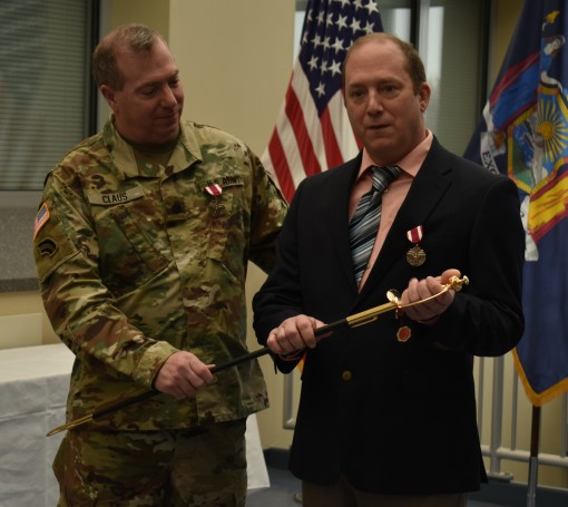 -N.Y. Army National Guard  Lt. Col. Joseph Claus presents his brother Master Sgt. Leonard Claus with a ceremonial Non-Commissioned Officers Sword during their dual retirement ceremony in Latham N.Y. Dec. 2 2017. The two brothers had a combined 63 years of
