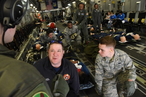 Airmen from various Air Force aeromedical evacuation squadrons work with civilians to move mock victims from a C-17 assigned to the New York Air National Guard's 105th Airlift Wing into a staged patient reception area during PATRIOT South 2018 at Jac