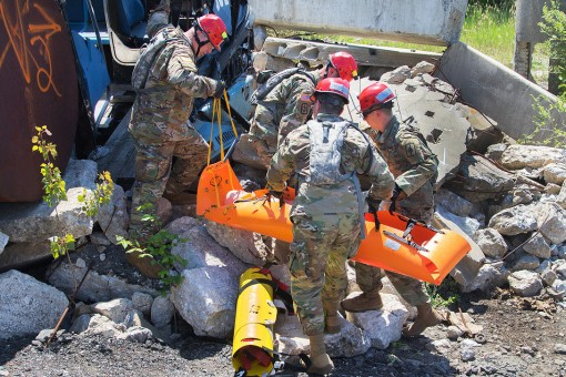 Soldiers assigned to the New York Army National Guard's 206th Military Police Company  transport a mock casualty from the debris after searching a simulated collapsed building during Vigilant Guard 18 at the Urban Search and Rescue Yard in Baltimore,