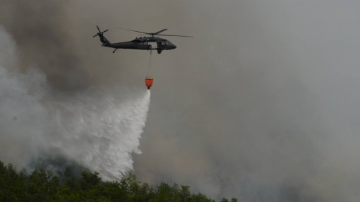 New York Army National Guard Soldiers assigned to 3rd Battalion 142nd Aviation Division deliver 660 gallons of water onto a forest fire in Flat Rock State Forest in Altona, N.Y. on Friday, July 13 2018. Two UH-60 aircrews  responded to a  fire that broke