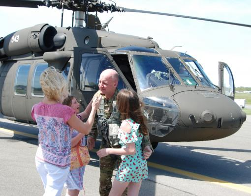 New York Army National Guard Col. Mark Slusar is greeted by his family-- his wife Sandra and daughters Abigail and Camryn-- following his final flight as an Army aviator at Aviation Support Facility 3 hanger on May 21 2020 in Latham New York. Slusar is re