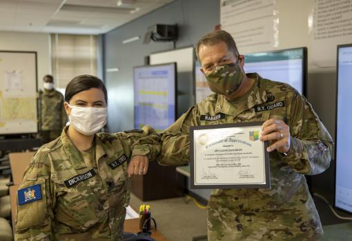New York Guard Brig. Gen. David Warager, commander of the New York Guard, bumps elbows with specialist Laura Dickinson after awarding a certificate of appreciation for her handwork during the COVID-19 pandemic at the emergency operations center on Camp Sm