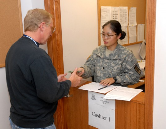 Spc. Jin Hui Jiang hands Richard Crogan his pay during a mission readiness exercise at Fort McCoy
