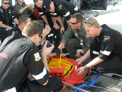 NY SPP - 103rd Rescue Squadron demonstrates the features of a rescue basket to members of the South African National Sea Rescue Unit